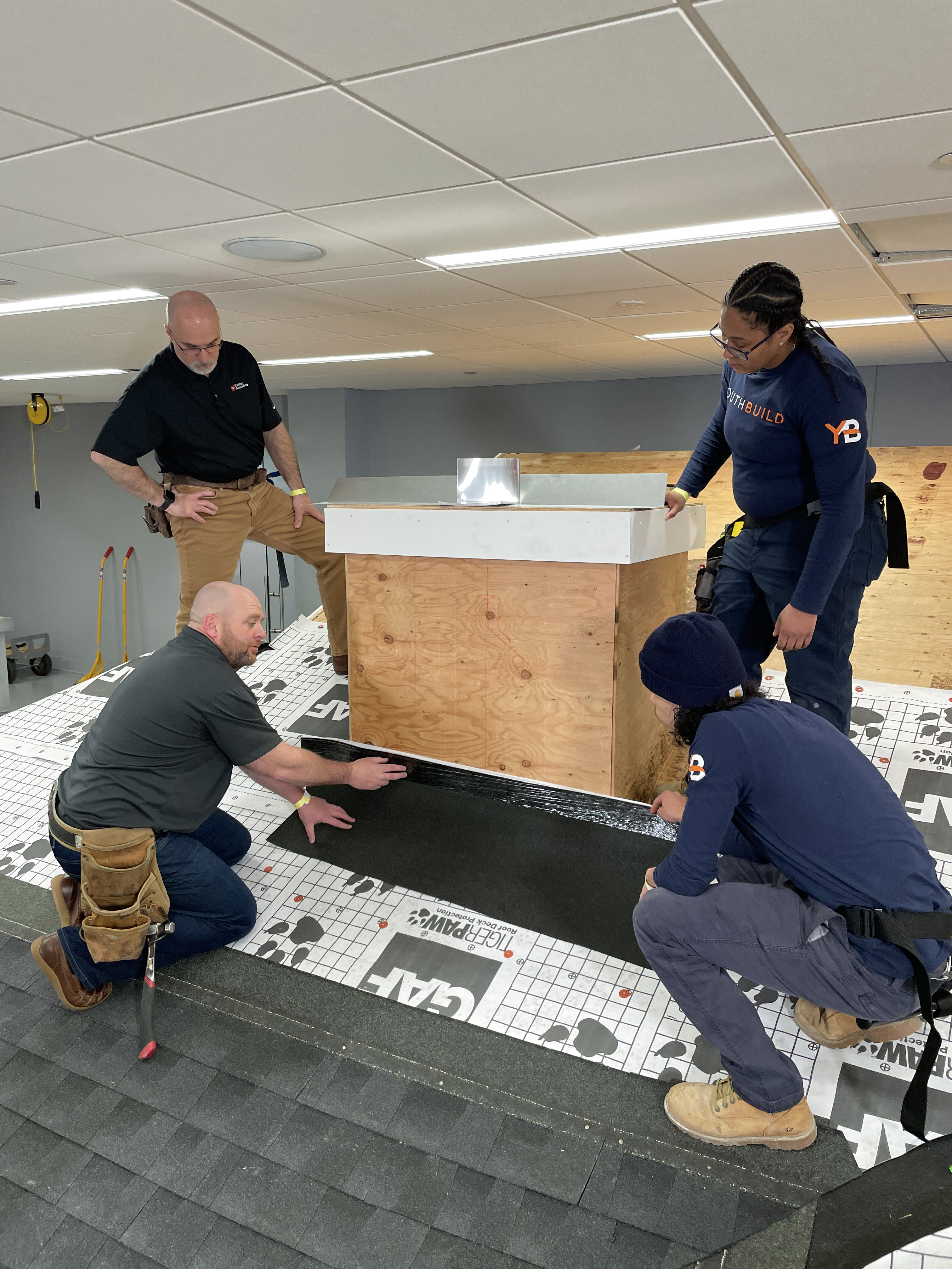 YouthBuild graduates getting hands-on roofing training.