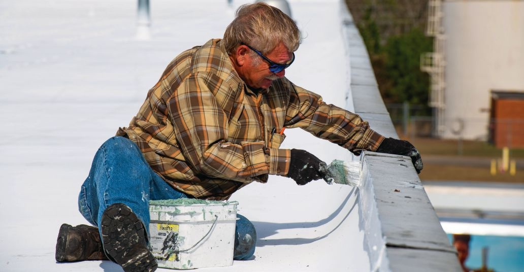 Application of acrylic topcoat at parapet wall detail. (Editor's note: There is a lower roof adjacent to the parapet that is not visible in this photo.)